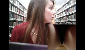 Dark-haired beauty fucking her pussy in a library