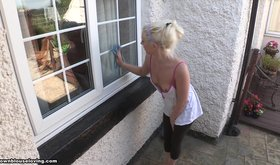 Blond-haired amateur cleaning windows and looking hot